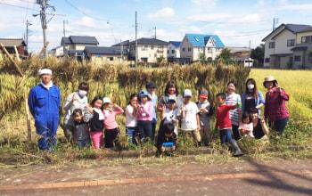 収穫したお米の前で記念撮影